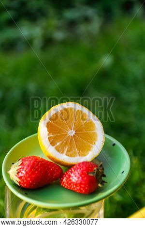 Defocus Close-up Saucer With Lemon And Two Strawberry Standing On Glass Jug Of Lemonade. Blurred Gra