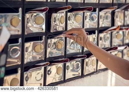 Mailboxes With Newspaper Inside. Woman Taking Away The Correspondence. News And Delivery Concept