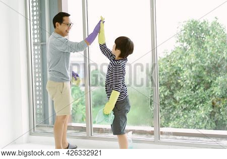 Happy Asian Father And Son Giving Each Other High-five After Cleaning Wiping Window Finished. Well D