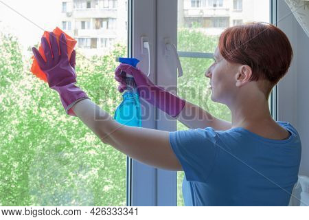 Young Woman With Short Hair In Rubber Gloves Washes Window In Her Apartment With Rag. Woman Holding