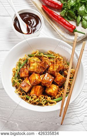 Sweet And Spicy Asian Noodle With Hoisin Baked Crunchy Tofu And  Green Bean  In A White Bowl With Ch