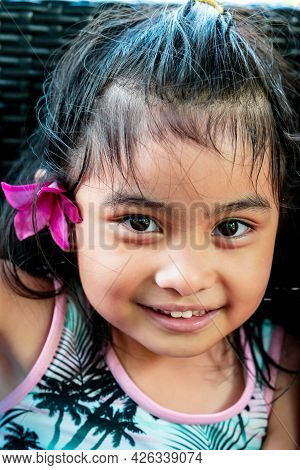 Little Girl With Large Pink Flower Behind Ear. Pretty Asian Child Portrait With Flower Behind Ear Sm