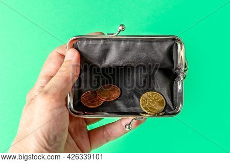 Open Wallet With A Change In Hand On A Green Background. Poverty Concept. Below The Poverty Line.