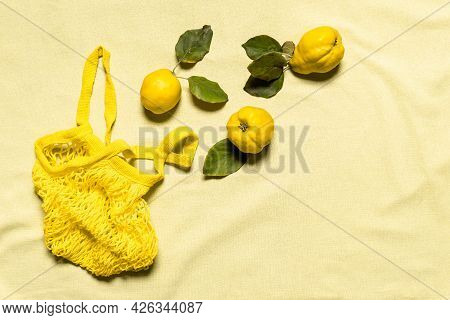 Three Quince Apples With Leaves And Yellow Mesh Bag On Wrinkled Pastel Colored Linen Background. Org