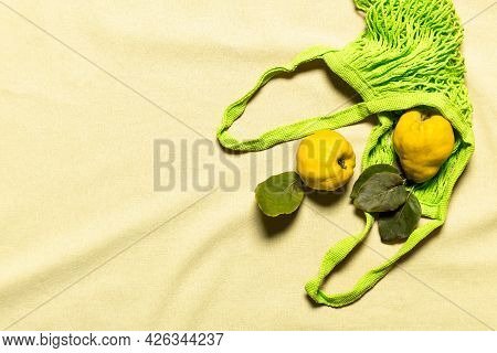 Quince Apples With Leaves In Green Mesh Bag On Wrinkled Natural Pastel Colored Linen Background. Org