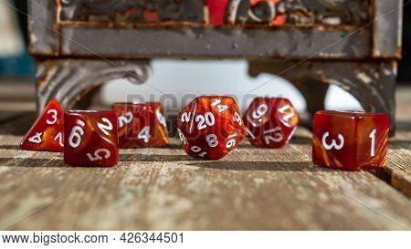 Close-up Of A Set Of Orange Marbled Roleplaying Dice Focused On The 20-sided Dice