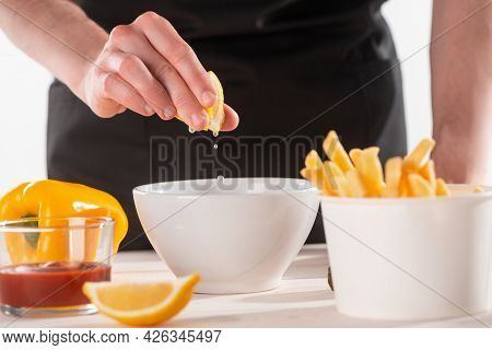Hand Squeezing Lemon Juice Into A Bowl With Ingredients