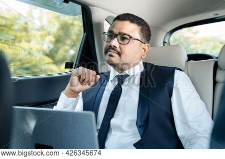 Thinking Serious Businessman With Laptop Travelling In Car Or Cab - Concept Of Thoughtful And Worrie