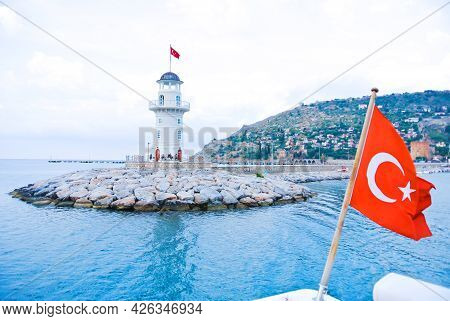 Sea Lighthouse On The Background Of The Turkish City Of Alanya. View From The Ship. Turkish Flag In