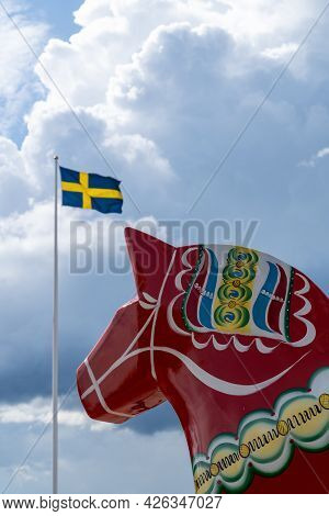 A Vertical View Of A Colorful Swedish Dala Horse And The Swedish Flag Under An Expressive Sky
