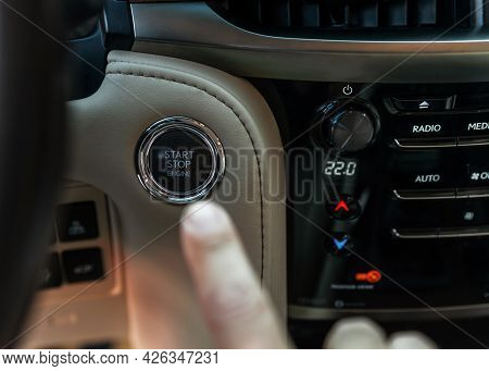 Finger Pressing Button The Start Button, Stop The Engine In The Luxury Car. The Man's Finger Is Pres