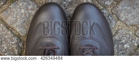 Comfortable Brown Leather Shoes For Men On Footpath Made Of Rocks Or Stones. Male Footwear
