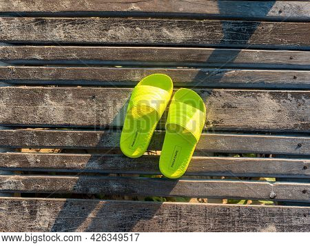 Cayo Coco, Cuba, 16 May 2021: Beach Yellow Bright Slippers Stand On A Wooden Platform Near The Ocean