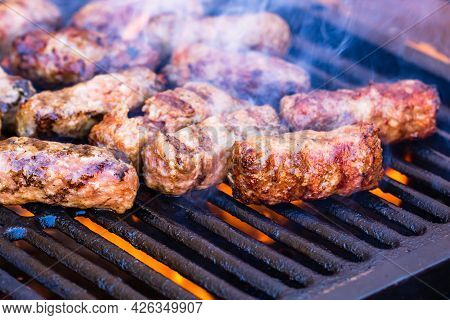 Preparing Meat Rolls Called Mici Or Mititei On Barbecue. Close Up Of Grill With Burning Fire With Fl