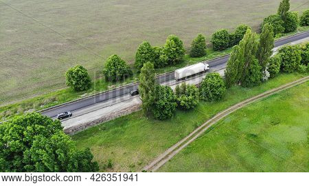Aerial. Transport Logistics Background. Truck Driving By The Highway Between Fields. View Above From