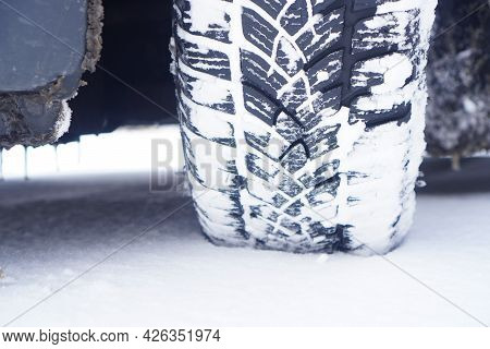 Driving In Snowy Weather.  Snow Covered Car Tire Close-up.