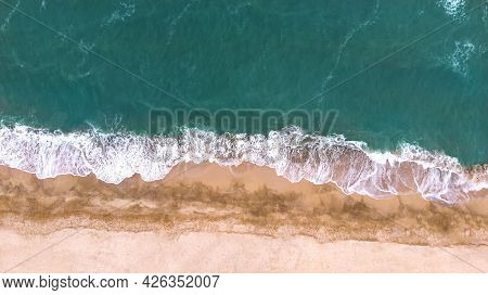 Aerial. Beautiful Sea Waves On A Sandy Beach. Top View From Drone.