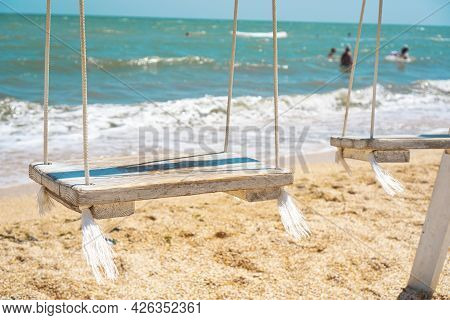 Swings With A Wooden Seats Against The Blue Sea