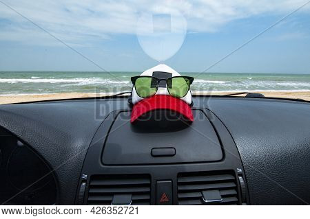 Traveling By Car Concept With Sea View Through The Car Windshield. Cap And Glasses Lie On The Car Da