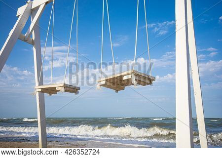 Swings With A Wooden Seats Against The Stormy Sea