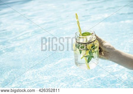 Lemonade Drink In Female Hand Against The Poolside.