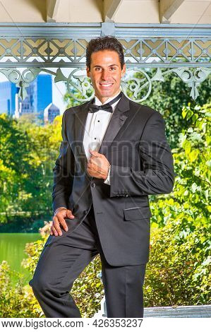 A Professional Executive Is Dressing In A Black Tuxedo, Smilingly Looking At You.