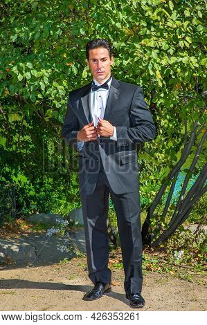 A Professional Executive Is Dressing In A Black Tuxedo, Confidently Looking At You.
