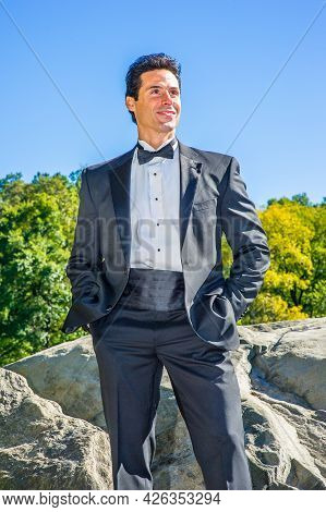 Dressing In A Black Tuxedo, Hands Putting In Pockets, A Professional Executive Is Standing By Rocks,