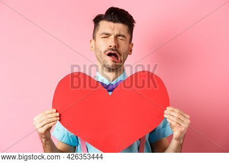 Valentines Day Concept. Sad And Lonely Man Feeling Heartbroken, Being Rejected, Showing Big Red Hear