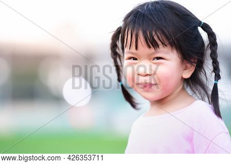 Portrait Of Asian Face Child Girl Sweet Smile. Happy Kid With Blurred Bokeh Background In The Evenin