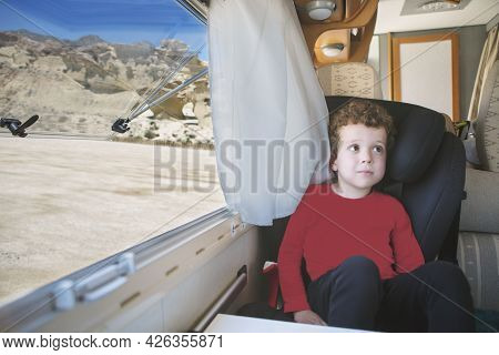 A Small, Curly-haired, Caucasian-looking Boy, Sitting By The Open Window Of His Parked Motorhome Wit