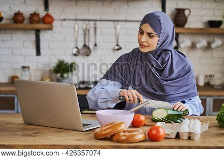 Arabian Woman Cutting Ingredients And Watching A Tutorial On Her Laptop