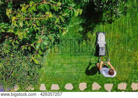 Caucasian Gardener Mowing Backyard Garden Grass Using Cordless Electric Grass Mower. Aerial View. Ga