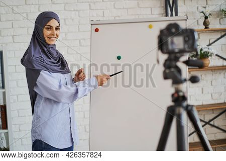 Muslim Business Lady Showing Something On A Board And Looking At The Camera