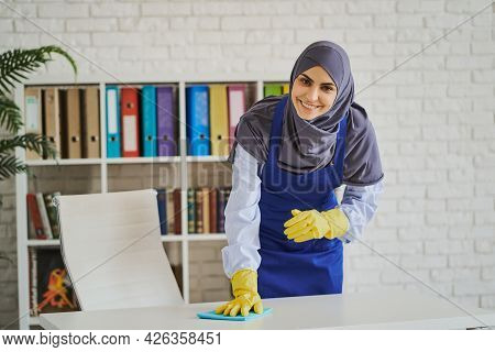 Smiling Arabian Woman Cleaning A Table In The Office