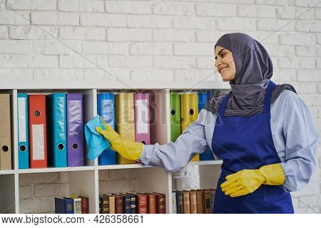 Young Arabian Woman Wiping Dust Off The Bookshelves With A Rug In The Office