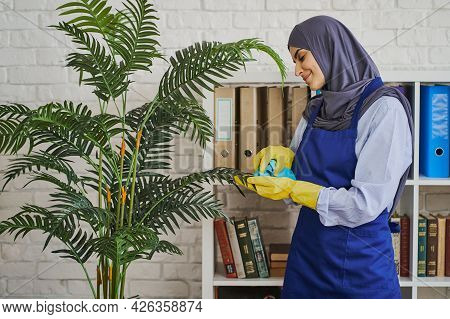 Arabian Woman Wiping Dust Off The Leaves In The Office And Smiling