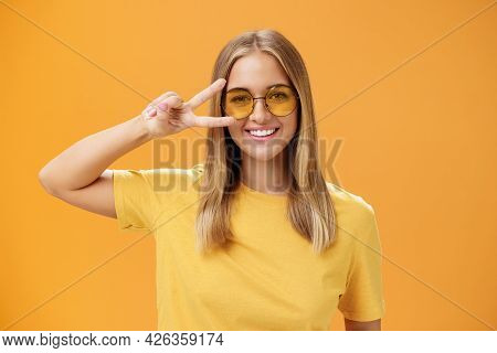Cute Optimistic And Friendly Young Caucasian Woman With Fair Hair In Yellow T-shirt And Sunglasses S