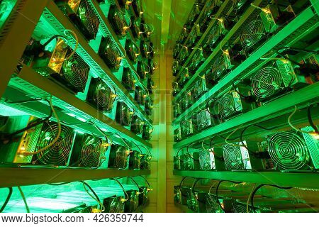 Bitcoin Miners In Large Farm. Asic Mining Equipment On Stand Racks Mine Cryptocurrency In Steel Cont