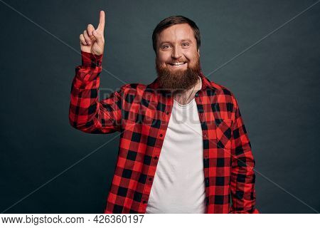 Impressed Bearded Hipster Man In Red Checkered Shirt, Pointing Up And Smiling Amused, Sharing Inform