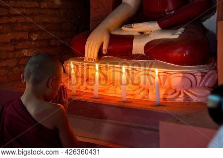 Bagan. Myanmar. November 26, 2016. A Boy Monk Dressed In A Bard-colored Kashaya With A Candle In His