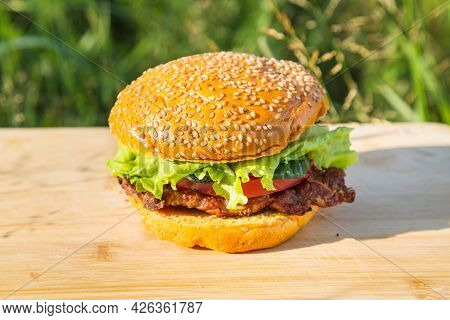Yellow Hamburger With Meat Steak, Tomato, Cucumber And Lettuce On The Background Of A Cutting Board
