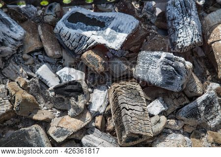 Smoldering Coals In The Grill With A Beautiful Pattern Of Black Wood Structure And A Silvery White F