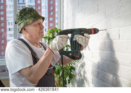 A Master Builder In Overalls Standing In The Loggia With A Puncher In His Hands Against The Backgrou