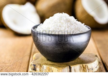 Grated Coconut, Coconut Shavings In A Clay Bowl, With Ripe Coconuts In The Background, On A Rustic W