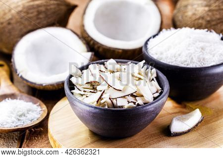 Coconut Chips, Shavings And Pieces Of Coconut Inside A Clay Bowl, With Many Ripe Coconuts In The Bac