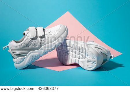 Macro Side View One White Childrens Running Shoe Stands On The Sole Of A Second Running Shoe Lying O