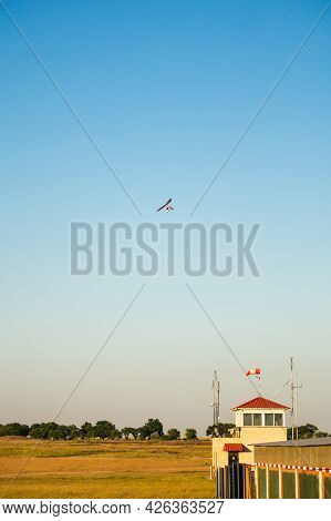 Motor Hang Glider With Passengers Flying Over Aerodrome In Clear Blue Sky