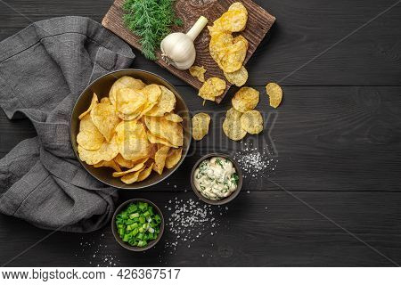 Potato Chips With Herbs, Salt And Sour Cream On A Black Background. Top View, Copy Space.