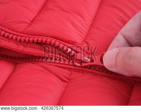 Close-up Shot Of A Zipper On A Red Jacket. Hand Unzipping A Red Jacket. Close Up.
